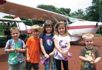 Chad Lincoln, Jake Weston, Brooke Lincoln, Leah Weston, and Cole Lincoln standing in front of one of the MAF planes Joey Lincoln flies