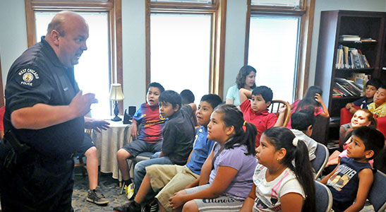 Rosie and kids listen to a West Chicago police officer who visited a Puente summer program at Main Park Apartments.